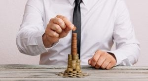 business-man-on-wood-table-building-stack-of-coins-SR8579E-300x200.jpg